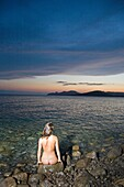 Back view of a naked woman sitting und looking at the sunset