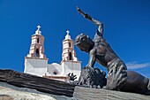 San Luis, Colorado - The Shrine of the Stations of the Cross is on a hill above town  The sculptures were created by artist Huberto Maestas  In the background is the Chapel of All Saints