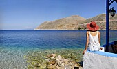 Woman admiring the sweeping view of the sea in the island town of Symi Greece