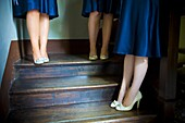 Cropped view of bridesmaids in blue satin dresses standing on stairwell