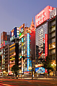 Neon blends with twilight and towering Karaoke Pubs in the popular Kabukicho area of the Shinjuku District in Tokyo, Japan.