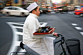 A young Japanese restaurant worker on a bicycle crosses Aoyama Avenue while delivering an order in the trendy yet upscale Omotesando District of Tokyo, Japan.