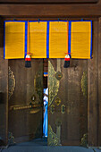 A detailed view reveals the fine craftsmanship in a wooden door with decorative metalwork and noren curtain inside the Outer Shrine of Meiji-Jingu Shrine, located in the Shibuya district of Tokyo, Japan.