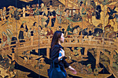 A young Japanese woman rushes by an old Edo-era woodblock print of the venerable Nihonbashi Bridge, which is being used as a mural for a construction site wall in the Nihonbashi district of central Tokyo, Japan.