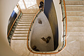 A Japanese woman checks her cellphone at the bottom of a gracefully winding staircase that descends to a small zen-style rock garden inside the Peninsula Tokyo Hotel in the Marunouchi District of Tokyo, Japan.