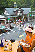 A stylish young Japanese woman relaxes upstairs in a cafe overlooking Harajuku Station and the greenery of Meji Jingu Shrine in the upscale Harajuku District of Tokyo, Japan.