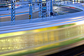Commuter trains swing around the tracks curving into Ueno Station in Tokyo, Japan in this telephoto view using a slow shutter speed to capture the blurring motion of the passing trains.