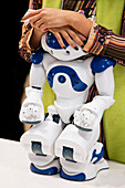 A staff member rests her hands on a demonstration service robot at the annual International Robot Exhibition, which attracts industry professionals as well as tech-geeks to Tokyo Big Sight, a modern convention center located in the Odaiba District o [...]