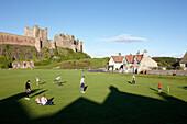 People playing on cricket ground underneath Bamburgh Castle, Bamburgh, Northumberland, England, Great Britain, Europe