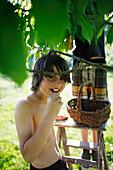 Boy eating a cherry, Klein Thurow, Roggendorf, Mecklenburg-Western Pomerania, Germany