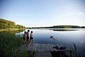 Family on jetty, woman jumping into lake Goldensee, Klein Thurow, Roggendorf, Mecklenburg-Western Pomerania, Germany