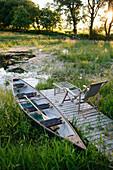 Pond with jetty and canoe, Klein Thurow, Roggendorf, Mecklenburg-Western Pomerania, Germany