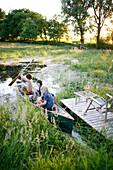 Three boys in a canoe on a pond, Klein Thurow, Roggendorf, Mecklenburg-Western Pomerania, Germany