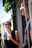 Couple standing beside a door, Klein Thurow, Roggendorf, Mecklenburg-Western Pomerania, Germany