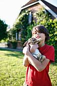 Boy holding rabbit in his arms, Klein Thurow, Roggendorf, Mecklenburg-Western Pomerania, Germany