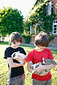 Boys holding rabbits in their arms, Klein Thurow, Roggendorf, Mecklenburg-Western Pomerania, Germany