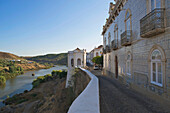 Street and houses above Rio Guadiana river at Mertola, Alentejo, north of the Algarve, Portugal, Europe