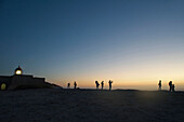 Light house and people as silhouettes on high cliff, Cabo de Sao Vicente, evening mood, Algarve, Portugal, Europe