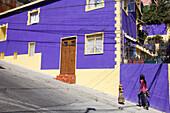 Girl walks up steep street past purple building, Valparaiso, Valparaiso, Chile, South America