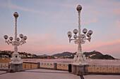 Street lamps at the seaside promenade at dusk, Playa de la Concha, Bahia de la Concha, San Sebastian, Donostia, Camino de la Costa, Camino del Norte, coastal route, Way of St. James, Camino de Santiago, pilgrims way, province of Guipuzcoa, Baskenland, Eus