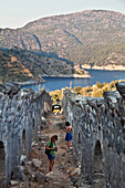 Woman taking photographs of the processional walkway on Gemiler Island in Fethiye gulf, lycian coast, Mediterranean Sea, Turkey