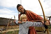 Child shooting with bow at the Viking village Haitabu, Schlei, Schleswig-Holstein, Germany, Europe