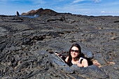 Woman in a lava hole on the lavafield of Isla Santiago, Galapagos, Ecuador, South America