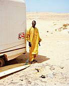 Senegalese musician in front of Joao's surf truck, surf spot Ponta Preta, west of Santa Maria, Sal, Ilhas de Barlavento, Republic of Cape Verde, Africa