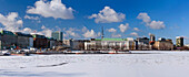 Panorama of the Binnen Alster covered in snow and ice and the buildings along the Neuer Jungfernstieg, Hamburg, Germany