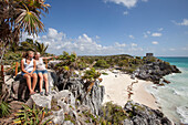 Two young girls and an iguana relaxing on a rock overlooking the beach, ancient Mayan buildings at the Tulum Ruins in the background, Tulum, Riviera Maya, Quintana Roo, Mexico