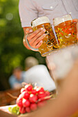 People with steins and radish at a beer garden, Munich, Bavaria, Germany, Europe