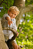 A boy sitting on the branch of a tree