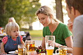 Family with child sitting at a table in a beer garden, lake Starnberg, Bavaria, Germany, Europe