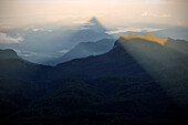 Pyramid shaped shadow at sunrise at Adam's Peak Sri Pada, view of the surrounding mountains, shadow from mountain peak, Mountain Region, Sri Lanka
