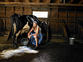 Milkmaid and cow in barn with spilt milk. Young woman sitting next to cow in barn. There is spilt milk on the floor. Woman and cow is looking at camera.