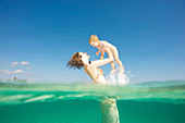 Mother lifting toddler up from water. Woman lifting young boy up in the air from crystal clear sea. Shot from both above and below water. Underwater shot.