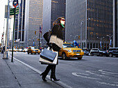 Elegant woman in New York street. Woman in New York street. She is holding shopping bags, looking across road.