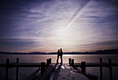 Couple at end of snowy pier at sunset