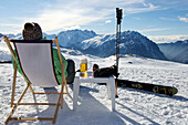 Skier relaxing with a beer. Skier relaxing with a beer on a deck chair on piste.