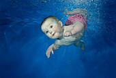 Female baby swimming underwater