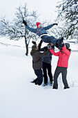 Young people having fun in the snow. Group of young people throwing a girl in the sky in snowy landscape smiling and laughing.