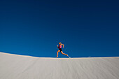 Young Woman Running over sand dunes. Young Woman Running over sand dunes.