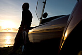 Older Man views sunset from car bonnet. Older Man views sunset from car bonnet