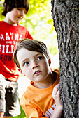 Two Boys Hiding Behind Tree
