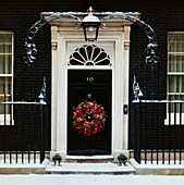 Door of Number 10 Downing Street in snow. UK Prime Minister´s front door with Christmas wreath in snow