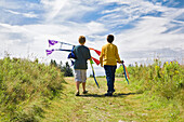 Boys walking with kite. Brothers walking down path with kite going toward blue sky