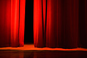 Lights on stage in theater. Red velvet curtains opening on lit stage in dark theater