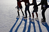 Teenagers ice_skating. Four teenagers ice_skating in a conga line outdoors