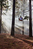 Gymnast using rings in forest. Gymnast using rings in forest