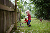 Toddler boy watering plants in backyard. Toddler boy watering plants in backyard